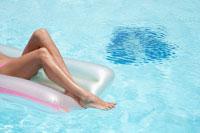 Woman lying on pool raft (focus on legs) 11021004653| 写真素材・ストックフォト・画像・イラスト素材|アマナイメージズ