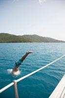 Mid adult man jumping from sailboat 11021004667| 写真素材・ストックフォト・画像・イラスト素材|アマナイメージズ