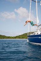 Mid adult man jumping from sailboat 11021004671| 写真素材・ストックフォト・画像・イラスト素材|アマナイメージズ