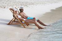 Young couple on lounge chairs on beach 11021004681  写真素材・ストックフォト・画像・イラスト素材 アマナイメージズ