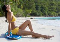 Woman sunbathing on surfboard at beach