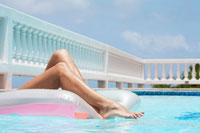 Woman lying on pool raft (focus on legs) 11021004737| 写真素材・ストックフォト・画像・イラスト素材|アマナイメージズ