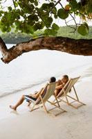 Couple on lounge chairs on beach 11021004743  写真素材・ストックフォト・画像・イラスト素材 アマナイメージズ