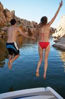 Couple jumping from motorboat to lake 11021004992| 写真素材・ストックフォト・画像・イラスト素材|アマナイメージズ
