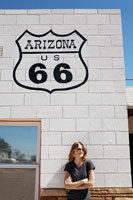 Young woman standing below Route 66 sign