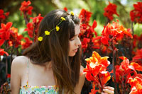 Young woman smelling red flowers