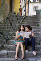 Two young women reading map on steps
