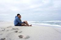 Couple sitting on sandy beach 11021005422  写真素材・ストックフォト・画像・イラスト素材 アマナイメージズ