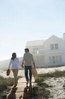 Couple walking towards house on beach 11021005440  写真素材・ストックフォト・画像・イラスト素材 アマナイメージズ
