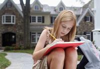 Girl doing homework near house