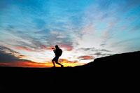 Male hiker playing bugle at sunset