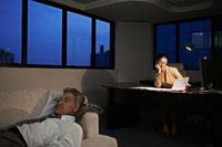 Woman working late, man sleeping on sofa