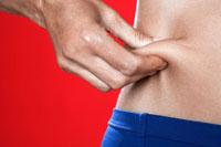 Woman pinching skin around abdominals