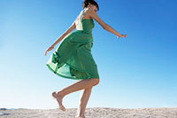 Young woman in dress running on sand