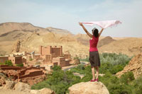 Woman Holding Up Scarf near Ruins
