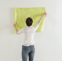 Young Woman Holding Wallpaper on Wall