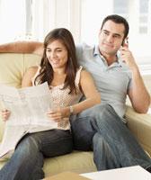 Couple Reading and Phoning on Sofa 11021007267  写真素材・ストックフォト・画像・イラスト素材 アマナイメージズ
