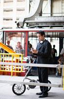 Businessman Using Cell Phone at Station 11021007965| 写真素材・ストックフォト・画像・イラスト素材|アマナイメージズ
