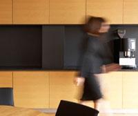 Mid-Adult Businesswoman walking in Kitchen