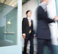 Two Businesspeople Walking Through Door 11021008301| 写真素材・ストックフォト・画像・イラスト素材|アマナイメージズ