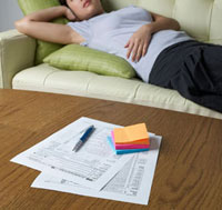 Tax Forms on Table, Woman Lying in Background