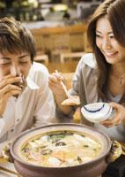 居酒屋で鍋料理を食べるカップル