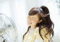 扇風機の前の女性
