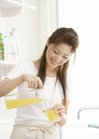オレンジジュースを注ぐ女性