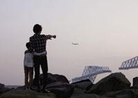 飛行機を眺める父と息子