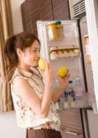 冷蔵庫から食材を選ぶ女性
