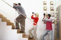 階段で双眼鏡をのぞく男女