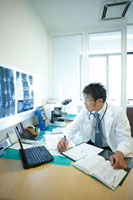診察室で仕事をする医師