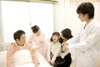 病室で夫を見舞う妻と子供 男性医師と看護師