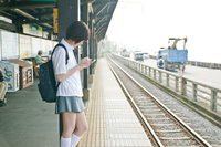 駅のホームでスマホをさわる女子高生