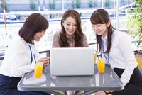 オープンカフェでパソコンを開くビジネスウーマン