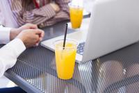 テラス席のノートパソコンとジュース