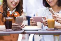 オープンカフェでスマホを操作する女性 11023017794| 写真素材・ストックフォト・画像・イラスト素材|アマナイメージズ