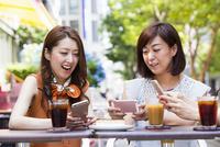オープンカフェでスマホを操作する女性 11023017795| 写真素材・ストックフォト・画像・イラスト素材|アマナイメージズ