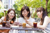オープンカフェでスマホを操作する女性
