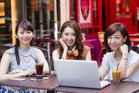オープンカフェでパソコンを開く女性