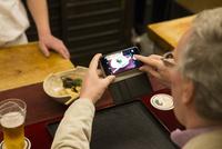 料理の写真を撮る外国人
