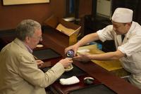 外国人に日本酒を注ぐ板前