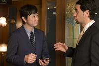 会話するスーツ姿の外国人と男性
