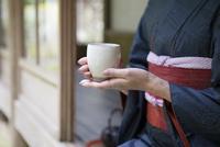 お茶を持つ着物姿の女性