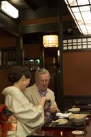 外国人に日本酒を注ぐ着物姿の女性