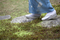 石畳の上を歩く着物姿の女性の足元
