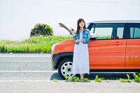 故障した車の前で鍵を持って立つ女性