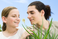Young man and preteen girl smelling flowering aloe plant