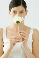 Woman smelling gerbera daisy, portrait