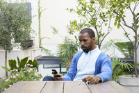 Man seated at table in courtyard making phone call